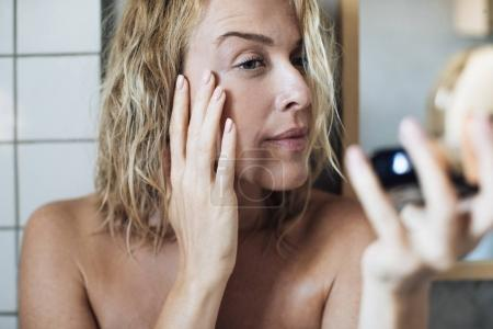 Woman Looking Herself in Mirror