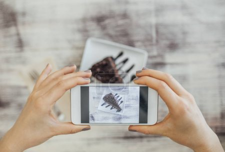 Photo for Hands of a woman taking photo of chocolate cake with her cell phone. - Royalty Free Image