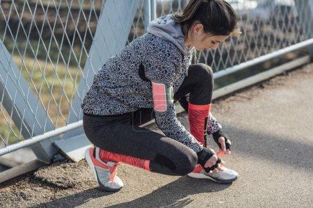 Sportswoman Tying a Shoe