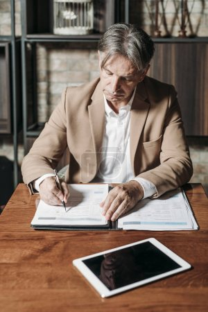 Mature Businessman Writing