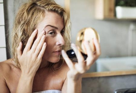 Woman Looking Her face in The Mirror