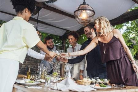 Photo for Group of smiling people cheering with wine and rising glasses on celebration at restaurant. - Royalty Free Image