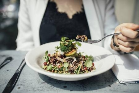 Photo for Hand of unrecognisable woman eating vegetarian salad. - Royalty Free Image