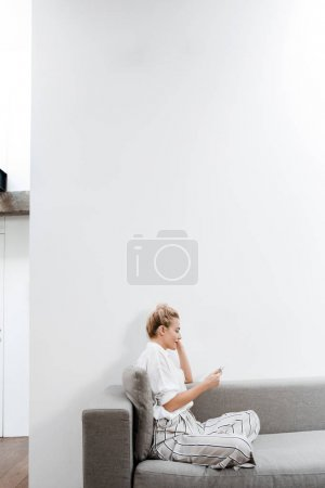Photo for Pretty blonde Caucasian woman sitting on couch at home and typing on smartphone. - Royalty Free Image