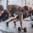 Group of men and women doing workouts together at ...