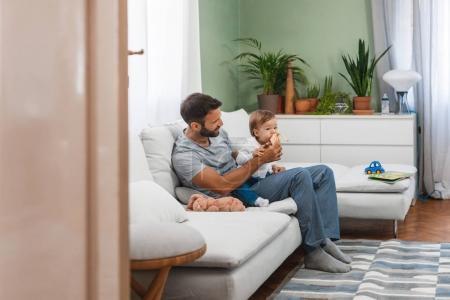 Photo pour Père de nourrir son fils à la banane à la maison. - image libre de droit