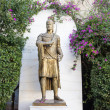 Bronze greek statue on pedestal in green bushes...