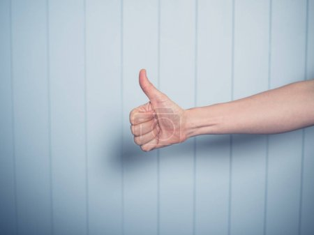 Photo for A young female hand is displaying thumbs up gesture - Royalty Free Image