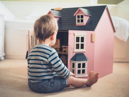 Photo pour Un petit garçon mignon et confiant dans le sexe brise les stéréotypes et les attentes socialement imposées en jouant avec une grande maison de poupée rose et en s'amusant - image libre de droit