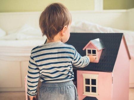 Un lindo niño seguro de género está rompiendo estereotipos y expectativas socialmente impuestas al jugar con una gran casa de muñecas rosa y pasar un buen rato