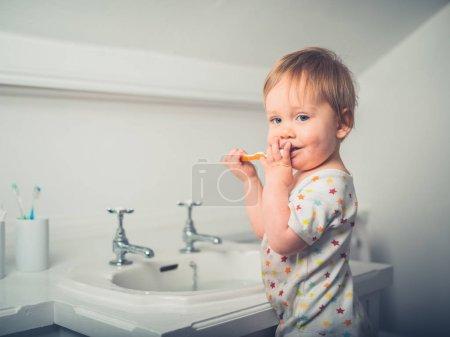 Photo pour Un petit garçon mignon se brosse les dents près de l'évier dans une salle de bain - image libre de droit