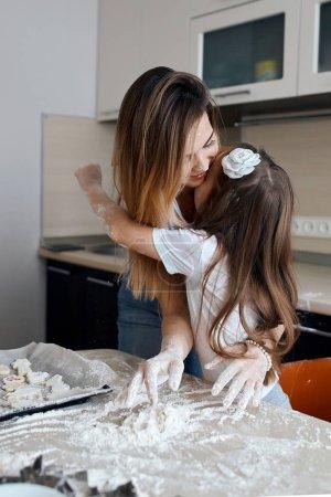 Photo pour Belle petite fille et sa mère appréciant le temps dans la cuisine, gros plan photo. la tradition familiale. liens forts, relations, amitié - image libre de droit