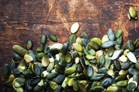Photo for Pumpkin seeds over wood background with copy space - Royalty Free Image