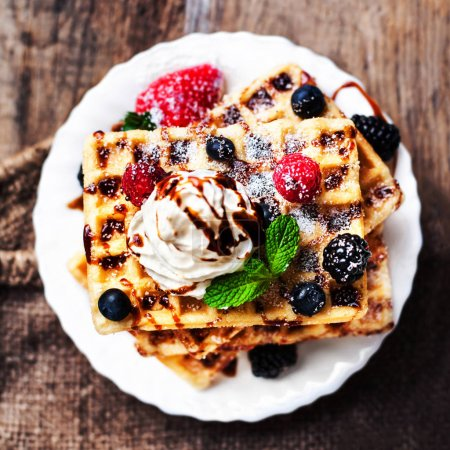Photo for Belgian waffles with mint leaves, strawberries and chocolate sauce on rustic table - Royalty Free Image