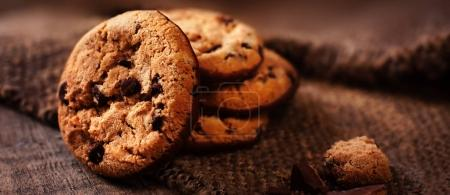 Photo for Chocolate chip cookies  on burlap  background macro. Freshly baked choco cookie close up - Royalty Free Image