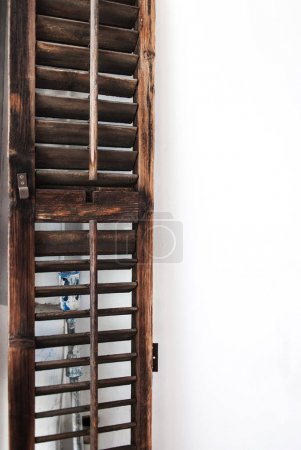 Dark old  wooden shutter door and white wall.  Grunge wall background with copy space
