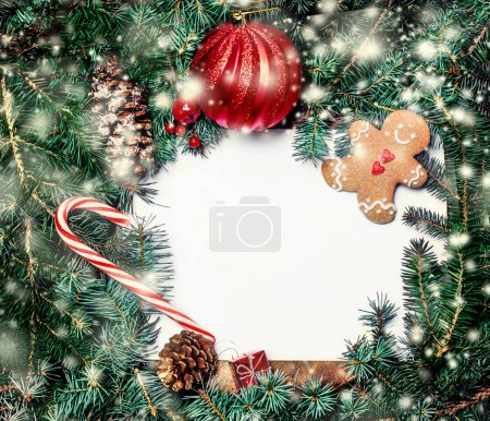 Christmas border with fir branches, red baubles, pine cones and other ornaments on wooden vintage board, copyspace