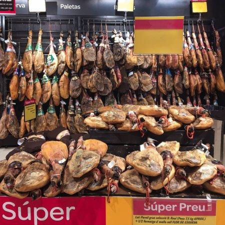 BARCELONA, SPAIN - SEPTEMBER 09, 2017: Jamon Serrano legs MEAT hanging  in a shop. Traditional Spanish ham Iberico