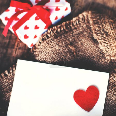Valentines day  Gift box with red bow ribbon, paper and hearts on wooden background