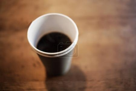 Black Coffee Americano in a paper cup on wooden table  vintage hipster style color tone