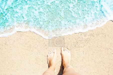 Soft wave of blue ocean on sandy beach Background with women feets, view from above. Tropical summer vacation concept