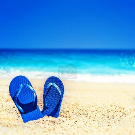 Summer holiday beach background with flip flops on a tropical beach. Slippers from a sand on a beach, funny concept