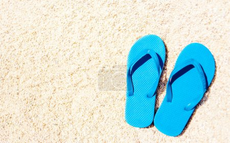 Summer holiday beach background with flip flops on a tropical beach. Slippers on a  sand with copyspace