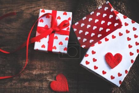 Valentines Day card with red hearts, gift box with red ribbon and place for text. Valentines Day concept Background for design
