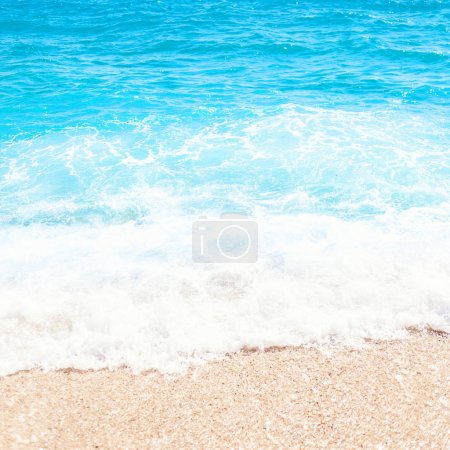 Soft wave of blue ocean on sandy beach Background with place for text. Tropical summer vacation concept