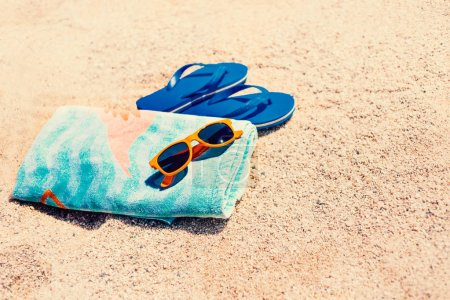 Blue  sandal flip flop,  sunglasses and towel  on yellow sand. Summer fun time and accessories on the beach,  summer vacations, copy space