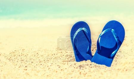 Summer Holidays in Beach Seashore. Summer vacation concept in vintage hipster style with blue  flip flop