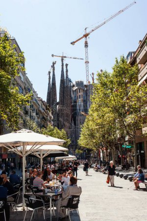 BARCELONA, SPAIN - SEPTEMBER 10TH, 2017: La Sagrada Familia - Catholic church in Catalonia, Barcelona, designed by famous  Catalan architect Antoni Gaudi and terrace cafe with people on street