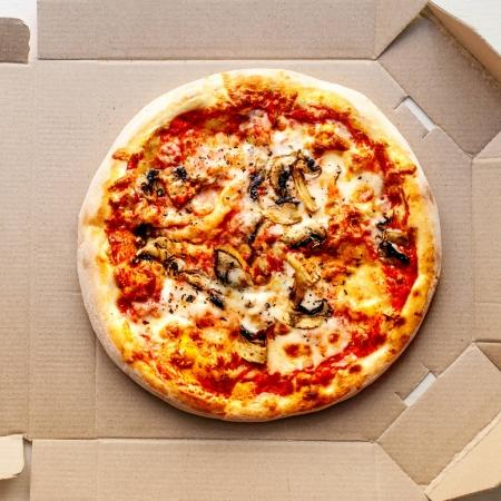 Photo pour Pizza dans une boîte en carton sur fond clair avec pepperoni, tomates cerises, fromage et sauce tomate. Livreur de pizza, menu. - image libre de droit