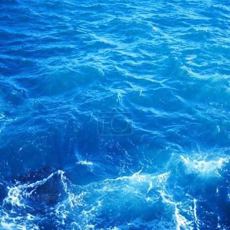Background image of aqua sea water surface with sunny reflections, aerial view. Ocean wave closeup