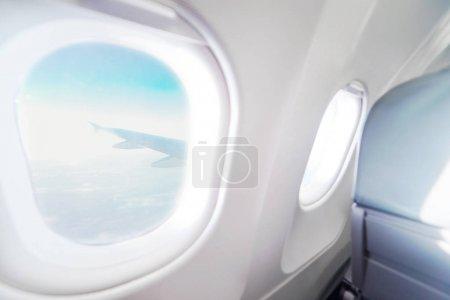 Photo pour Avion vue de la fenêtre à l'intérieur d'un avion. Plan de la fenêtre. Concept de destinations de vacances. Les sièges bleus clair et blanc intérieur avec vue sur le ciel et l'aile du plan - image libre de droit