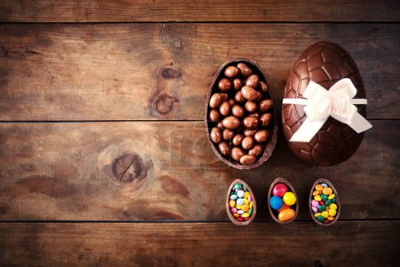 Photo for Chocolate Easter Eggs on dark Wooden Background with color ribbon bow - Royalty Free Image
