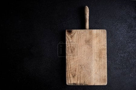 Photo for Old chopping cutting board on black stone background - Royalty Free Image