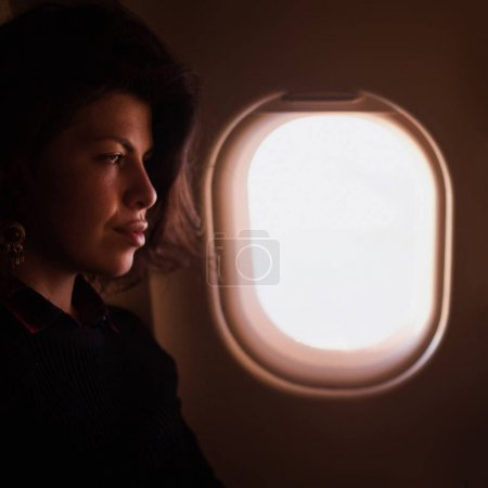 Young woman inside airplane sitting on passenger seat near window