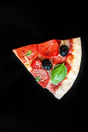 Slices of  Pizza with salami, ham cheese, basil leaf  and bacon,
