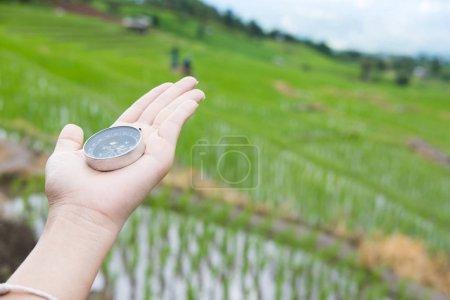 Photo pour Compas à la main avec rizière sur fond de nature de terrasse. voyage, voyage, voyages concept - image libre de droit