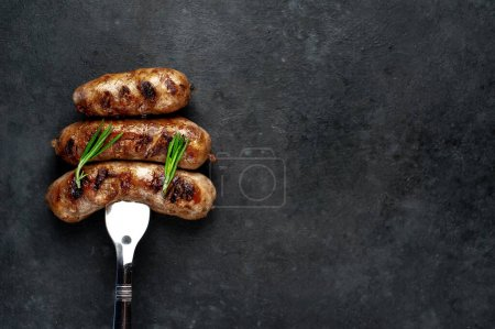 Photo for Grilled sausages on a meat fork on a stone background with copy space for your text - Royalty Free Image