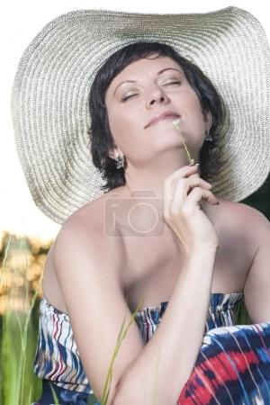 Portrait of Smiling Caucasian Brunette Woman Posing in Big Round Hat Outdoors.