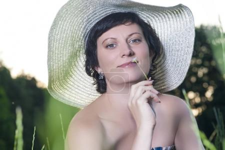 Portrait of Smiling Caucasian Brunette Woman Posing in Big Round Hat Outdoors