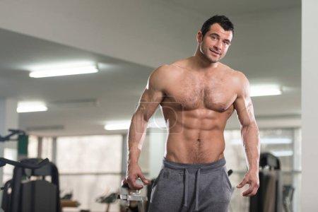 Behaarter Mann lässt Muskeln spielen