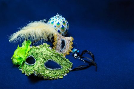 Theatrical masks with ornaments, a feather and a sphere