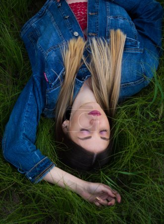 Photo for Girl with beautiful hair lying on her back in the green, juicy grass. Warm spring evening - Royalty Free Image