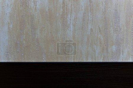 Photo pour Le mur est décoré de plâtre de pêche clair avec nacre et bande horizontale non large de bois foncé par en bas . - image libre de droit