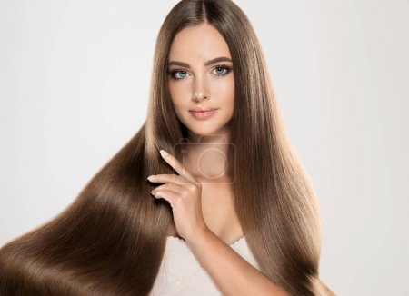 Photo for Beautiful girl with brown long straight shine health hair on background - Royalty Free Image