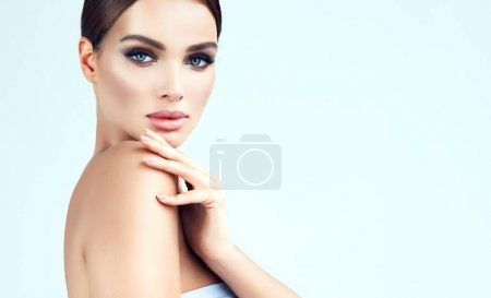 Beautiful young woman with clean fresh skin, bare sholders and elegant gesture. Close up portrait. Cosmetic, cosmetology and skin care