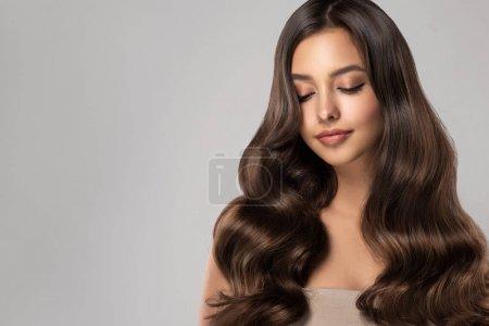 Photo pour Jeune femme aux cheveux bruns et aux cheveux ondulés.Beau modèle avec une longue coiffure  . - image libre de droit